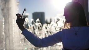 Маленькая девочка при длинные волосы представляя на камере, принимая фото около фонтана в городе HD, 1920x1080 движение медленное акции видеоматериалы