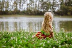 Маленькая девочка при длинные волосы сидя в траве рекой Стоковая Фотография RF