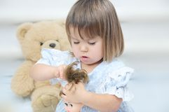 Маленькая девочка при кукла расчесывая играть волос Стоковое Фото