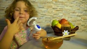 Маленькая девочка при курчавые светлые волосы делая вдыхание видеоматериал