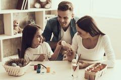 Маленькая девочка при молодые родители крася яичка стоковое фото rf