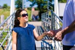 Маленькая девочка при солнечные очки входя в шлюпку и покупая билет стоковые изображения rf