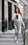 Маленькая девочка при тонкая диаграмма идя вне от сумок нося магазина бумажных стоковые фотографии rf