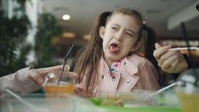 Маленькая девочка пробует сок моркови и гримасы с некоторым сток-видео