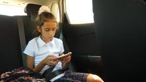 Маленькая девочка, пробуренная в автомобильном смотрящ вне окно через окно - отражение улицы, 4k, замедленное движение сток-видео