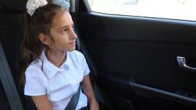 Маленькая девочка, пробуренная в автомобильном смотрящ вне окно через окно - отражение улицы, 4k, замедленное движение акции видеоматериалы