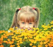 Маленькая девочка пряча за цветками стоковое фото rf