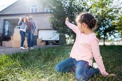 маленькая девочка развевая к родителям пока сидящ на траве  стоковое фото