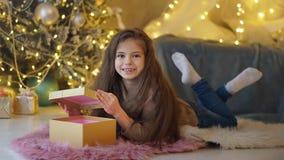 Маленькая девочка распаковывает подарки рождества стоковая фотография