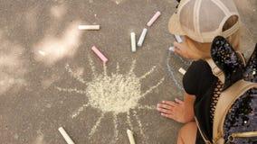 Маленькая девочка рисует мел на асфальте Ребенок рисует солнце в парке акции видеоматериалы