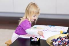 Маленькая девочка рисует на бумаге Стоковое Фото