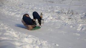 Маленькая девочка свертывает вниз холм в санях в снеге девушка играя в зиме в парке рождества движение медленное сток-видео