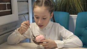 Маленькая девочка сидит в кафе и ест мороженое шоколада Конец-вверх, высокая деталь видеоматериал