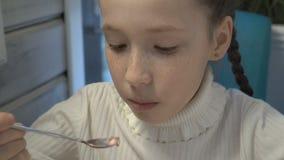 Маленькая девочка сидит в кафе, смешивает мороженое в чашке и ест ее Конец-вверх, высокая деталь акции видеоматериалы