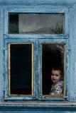 Маленькая девочка сидит в старой хате на окне на котором краска увяла Стоковое Изображение