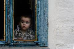 Маленькая девочка сидит в старой хате на окне на котором краска увяла Стоковые Изображения RF