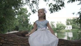 Маленькая девочка сидит на дереве видеоматериал