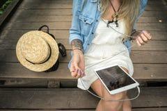 Маленькая девочка сидит на деревянных шагах и держит таблетку в ее руках, рядом с ей кожаный рюкзак и соломенная шляпа Стоковые Изображения