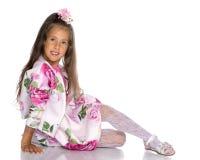 Маленькая девочка сидит на поле стоковое изображение
