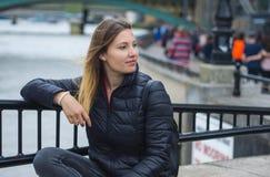 Маленькая девочка сидит на стене на реке Темзе в Лондоне Стоковое фото RF