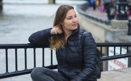 Маленькая девочка сидит на стене на реке Темзе в Лондоне Стоковые Изображения