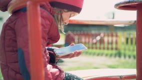 Маленькая девочка сидит на carousel в спортивной площадке и app использования на smartphone видеоматериал