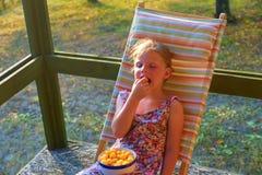 Маленькая девочка сидит на deckchair сада на verandah Малая девушка ест закуски приправленные сыром в стоковые изображения
