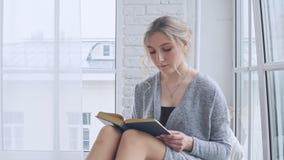 Маленькая девочка сидит на windowsill и читает книгу акции видеоматериалы