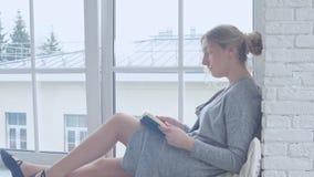 Маленькая девочка сидит на windowsill и читает книгу сток-видео