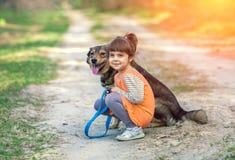 Маленькая девочка сидит с собакой на пути стоковая фотография rf