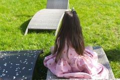 Маленькая девочка сидя в саде яблока цветения установьте ослаблять стоковое изображение