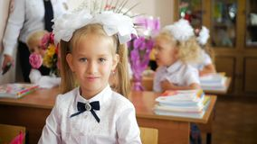 Маленькая девочка сидя и изучая на школьном классе Портрет симпатичной девушки смотря камеру на уроке видеоматериал