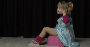Маленькая девочка сидя на горшочке и смотря ТВ видеоматериал
