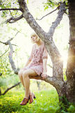 Маленькая девочка сидя на дереве Стоковые Изображения RF