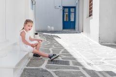 Маленькая девочка сидя на крылечке, Греция Стоковые Фото