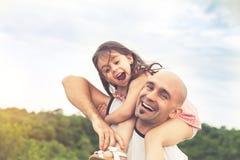 Маленькая девочка сидя на плечах ` s отца стоковые изображения