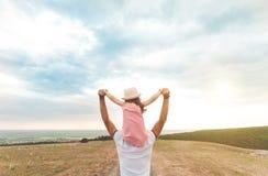 Маленькая девочка сидя на плечах ` s отца стоковые фото