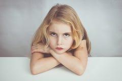 Маленькая девочка сидя на таблице и смотря ко мне с ненавистью стоковые фотографии rf