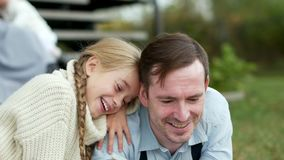 Маленькая девочка сидя обнимающ ее отца и читающ книгу сток-видео