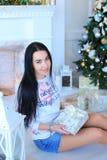 Маленькая девочка сидя около дерева Christmass и держа настоящий момент стоковое фото