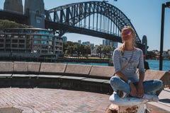 Маленькая девочка сидя около моста гавани Стоковые Изображения RF