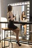 Маленькая девочка сидя с бокалом вина стоковые фото