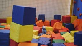 Маленькая девочка скача в бассейн с красочными мягкими кубами в развлекательном центре батута сток-видео
