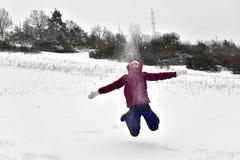Маленькая девочка скачет вверх в высоту от утехи в снеге стоковое фото