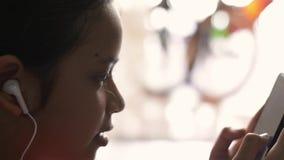 Маленькая девочка слушая музыку от мобильного телефона
