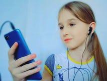 Маленькая девочка слушая музыку через телефон стоковое изображение rf