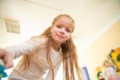 Маленькая девочка смотрит верхнюю часть камеры вниз стоковое фото