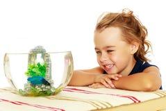 Маленькая девочка смотрит рыб которые плавают в аквариуме Стоковое Изображение RF