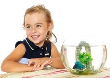 Маленькая девочка смотрит рыб которые плавают в аквариуме Стоковая Фотография RF
