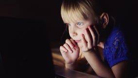 Маленькая девочка смотрит шарж на компьтер-книжке Светящий экран компьтер-книжки освещает сторону ` s ребенка видеоматериал